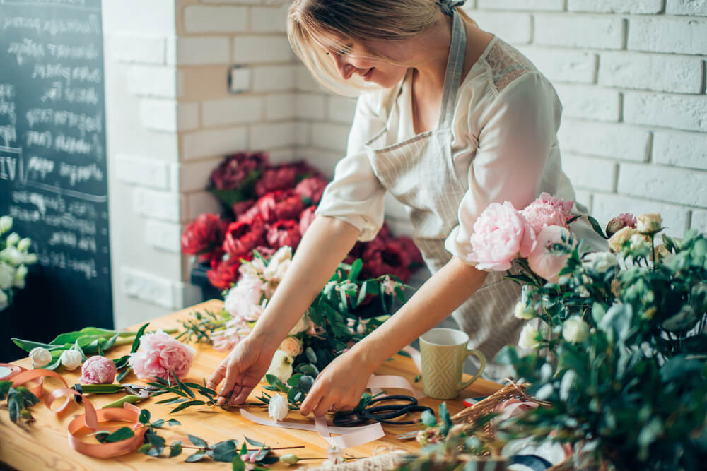 Woman organizing flowers in small business flower shop